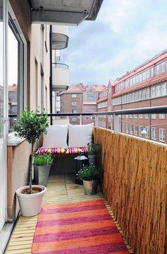 En bænk med farvestrålende puder giver dig både siddeplads og opbevaring på den lille altan