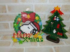 ★★アイロンビーズ★ スヌーピー風クリスマスリース ★アイロンビーズで作りましたクリスマスリースです。本体サイズ縦約15cm×横約15cm(上部にひもを取り付ける部分が他についています)文字プレート縦約5cm×横役7.5cm単品で飾り付けることもできますし、文字プレートを後付けして飾ることも可能です。後付けする場合は市販の接着剤(木工用ボンドや普通の工作用ボンド、両面テープなど)をご使用下さい。クリスマスシーズンの飾りにいかがですか?プレート複数ご落札の場合には送料はこちらで負担致します。※クリックポ...