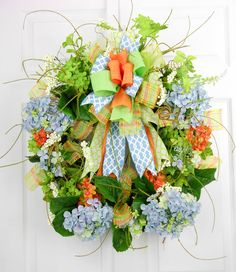 Topped with a centered Terri Bow, this hydrangea wreath is a beautiful statement of summer flowers. There are blue, white, green and orange realistic hydrangeas in various sizes, as well as berry stem