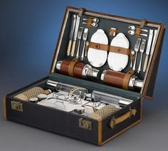 Rolls-Royce picnic case designed in 1905; contains a picnic service for four, two leather-wrapped stainless steel thermoses, four dishes with recesses for teacups, a matchbox and a variety of utensils including forks, mustard spoons, butter spoons and bone-handled knives.
