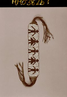 Loomwoven imitation-wampum glass bead garter, consisting of seventeen rows of glass beads, white ground and black figures, three plain ones seperated by two with skirted costume [skirts or frock coats] indicating, perhaps, an alliance between three native units and two frock-coated European entities. The garter is edged with rows of white beads, added on as the wefts turn the corner to resume their way accross the warps in the opposite decoration. Three wool twines are used; 14 warps are of…