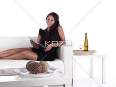 young woman reading on a couch - Shot of a young woman reading on a white couch.