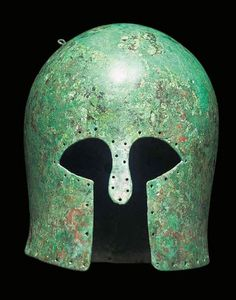 Corinthian helmet, second half of 7th century B.C. Of deep domed form, with nose-guard and pierced with multiple holes around the perimeter, pierced attachment holes on crown and remains of pierced loop at rear, 23.5 cm high. Private collection, from Christie's auction
