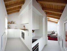 Cocina blanca con techo abuhardillado de madera