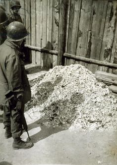 American Troops of the Third Army view a pile of ashes outside the crematorium of Buchenwald Prison Camp (b/w photo)