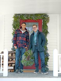 Designers Jaithan Kochar (left) and @Eddie Persson Persson Ross deck out the front porch of their New England home with a garland and wreath of juniper, spruce, and cedar.