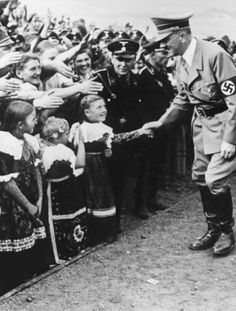 Hitler greeting three very happy little ones while others want to shake his hand. (via aryanismorethancolourofskin)