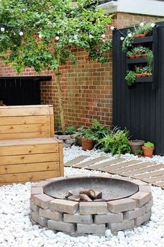 DIY fire pit in a modern garden with black fencing | Growing Spaces