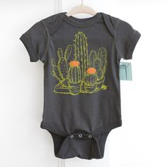 This 100% cotton baby one piece has been screen printed with a hand drawn cactus print. This onesie will make a great baby shower gift or the perfect outfit for your baby. Printed with bright green an