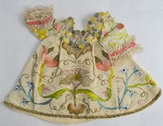 Infant's dress, Spain, 18th century. Cream silk embroidered with an orchid, tulips, spring flowers and strawberries, worked in multicoloured silk and gilt thread, pink silk ribbon and lace trim.