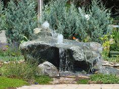 fontaine extérieure de jardin en pierre grise pour une ambiance rustique et végétation abondante