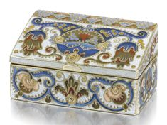 A FABERGÉ SILVER-GILT AND CLOISONNÉ ENAMEL BOX, PROBABLY FEODOR RÜCKERT, MOSCOW, CIRCA 1910    of podium form, the surface with polychrome shaded flowers and leafscrolls within cloison coils on pale blue-flecked grounds, the whole with dripped silver overlay, struck K.Fabergé in Cyrillic beneath the Imperial Warrant, 88 standard    width: 5cm, 2in.