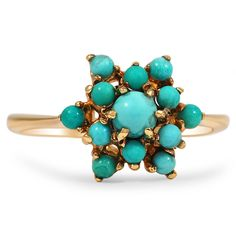 This Victorian-era ring presents thirteen striking turquoise cabochons in a beautiful pointed floral design atop a perfectly delicate yellow gold band.
