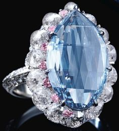 Fancy vivid blue diamond ring with pink and white diamonds. The center stone is an extremely rare modified pear double rose-cut fancy vivid blue diamond weighting 5 carats. The blue diamond is surrounded by 6.69 carats of briolette diamonds and brilliant cut pink diamonds. Via Diamonds in the Library.