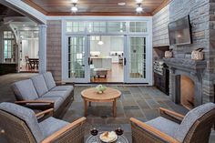 Covered patio with stone fireplace and BBQ. TV above outdoor fireplace. John Kraemer & Sons.