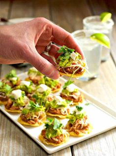 Chicken tostadas are a festive and delicious party food especially when they're bite size! Five layers of flavor piled on to a round tortilla chip (instead of traditional tostada shells). This version has refried beans, tender chicken with Mexican spices, cheese, guacamole, sour cream and fresh cilantro. But it's entirely versatile, swap in any ingredients you like!