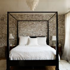 A brick wall and simple four poster bed create a masculine bedroom.