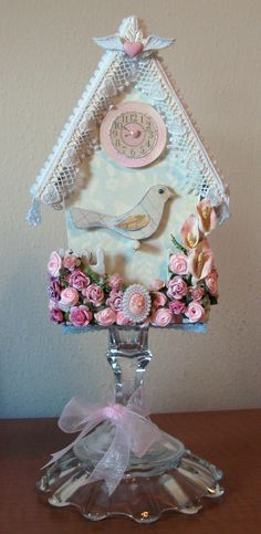 Such a fancy bird house!    The roses are a mix of Walmart and Michael's finds and the Calla Lilies, by Prima, can be found at McMahon Five Designs.  The pretty little cameo is from Webster's Pages and the heart with wings was in a bag of buttons bought at Michael's.
