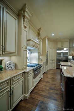 My favorite, anitque white distressed cabinets, hood, dark kitchen island, granite