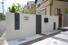 道路からエントランスまで続く壁にクラフトタイルを使ったシンプルモダンな門袖壁。