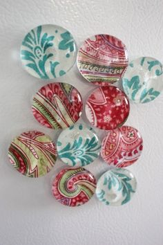 Decoupage fabric onto the back of a glass pebble and mount the pebble to a magnet. Cute!