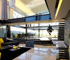As per the client's wishes, House Ber comes complete with an open, airy floor plan and four bedroom suites. Designed by Nico Van Der Meulen Architects, the Midrand, South African home consists of a rectangular shape that houses the living room, dining room, and kitchen, with the pool and koi pond surrounding it.