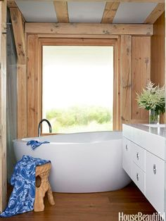 """The sculptural Waterworks tub is placed on a slight diagonal, with a view of the dunes in the bathroom of a Swedish-inspired Southampton beach house. """"This is a moment of romance and surprise,"""" Designer David Netto says, """"like a candlelit dinner in a barn."""" Dornbracht faucet. Porthault towel.   - ELLEDecor.com"""