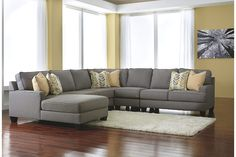 Indulge in modern relaxation with the inviting scale of a Chamberly 5-piece sectional. Sleek lines and legs give the profile a sophisticated look, while low track arms, supportive cushioning and soft feather-filled pillows create a place to lounge. Chic earth-tone upholstery fits in with contemporary color schemes and is easy care.