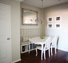Dining Room with storage - shorter backed upholstered banquette with a mirror above it.