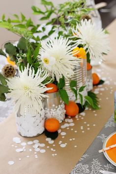 Confetti tin cans, white flowers with greenery and clementine oranges