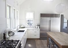 white kitchen with wood table island and contrast toe kick