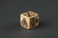A Sailors Scrimshaw Marine Ivory Gambling Dice Carved from a Sperm Whale Tooth  With designs for a heart, crown, club, spades, anchor and diamond, inlaid with pitch and red wax  Early 19th Century Size: 2.5cm sq – 1 ins sq