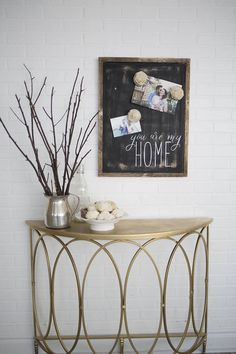 """A perfectly elegant way to showcase pictures of you and your loved ones. You Are My Home features hand painted lettering, recycled materials and distressed. Giving it a chalkboard feel, this sign will work well with any color scheme and home year round. Comes with board, and three magnet flowers.   Dimensions 19 1/2"""" wide  25 inches tall"""