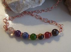 """Men's / Unisex Copper Chakra Necklace by AlisonsGemstones on Etsy20"""" Men's / Unisex Copper Chakra Necklace  Achieving personal peace and balance using the energy of a variety of natural stones to represent the 7 energy centers  This Necklace uses Garnet, Carnelian, Tigereye, Jade, Sodalite, Amethyst and Fluorite. The chain is hand wrapped copper. Copper jewelry has been worn for years by people with joint pain with the thought that the body absorbs the essential mineral when needed."""