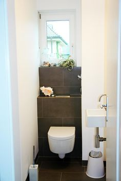 Guest Toilet Ideas: 18 Top Examples That Inspire! - Narrow guest bathroom with dark gray tiles on the floor and behind the toilet, ramp with storage ar - Small Toilet Room, Guest Toilet, Downstairs Toilet, Small Bathroom Storage, Storage Spaces, Neutral Bathroom, Guest Bathrooms, Bathroom Ideas, Grey Tiles