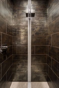 Slate gray tile surrounds this stunning, contemporary walk-in shower. A long strip of white tile extends down tot he white tiled floor, adding contrast and visual interest.