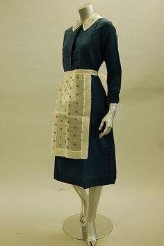 A maid's uniform, 1939, of blue wool with embroidered muslin headband, 2 collars and apron, with note stating `The afternoon uniform of my last house parlour maid, Hilda Edwards, 1939