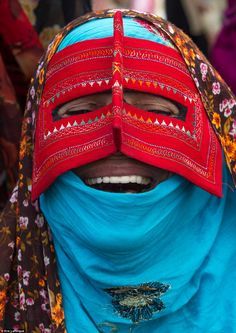 A laughing bandari woman wearing a traditional mask at Panjshambe Bazaar. Men associate ma...