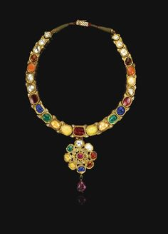 An enamelled and gem-set Navratna necklace, India, late 18th century. Estimate 10,000 — 15,000 GBP. Lot sold  15,000 GBP. Photo Sotheby's  comprising linked elements of octagonal form supporting a floral rosette pendant, each set with gemstones of varying colours, including white sapphires, pink coral, emeralds, rubies and diamonds, the reverse decorated with flowering plants and floral rosettes in white, green and red enamel, cabouchon ruby drop pendant; 19cm. length