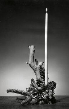 Een kerststuk van een boomstronk opgemaakt met een lange witte kaars en  onderop  dennentakjes  met dennenappels. 1952. Plaats onbekend.