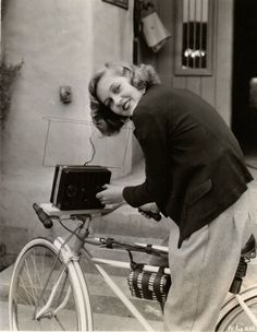 """Patricia Ellis rides a bike, plays a radio. MUSIC WITH HER BIKE RIDES: PATRICIA ELLIS HAS A RADIO WITH BATTERIES AND EVERYTHING ATTACHED TO HER BICYCLE SO THAT SHE CAN LISTEN TO MUSIC ON THE AIR WHEN SHE RIDES HOME FROM THE FIRST NATIONAL STUDIO WHERE SHE IS FILMING """"THE WORLD CHANGES."""" First National Pictures, 1933"""