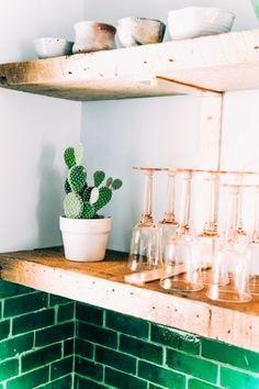 深いエメラルドグリーンのタイルとラスティックで重厚なキッチンの棚