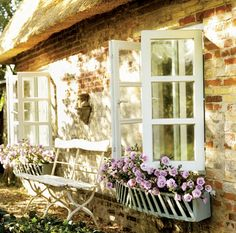 I love this quaint little cottage with the windows flung wide open and the sweet window boxes!