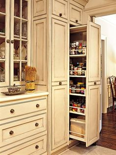 For added interest and to showcase the homeowner's dish collection, the cabinets incorporate both solid and glass doors. One wall is devoted to service, storing additional dishes, crystal, and other favorite accessories. Two large pantry-type units slide into the service wall. (Photo: Photo: Laurey W. Glenn)