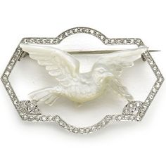 EDWARDIAN MOTHER OF PEARL DOVE BROOCH. An Edwardian mother-of-pearl and diamond dove brooch, with a dove, carrying and olive brooch, carved in mother-of pearl, with a surround, pavé set with rose-cut diamonds, with millegrain edges,Mounted in Platinum. In a Gass & Co, Regent Street box.