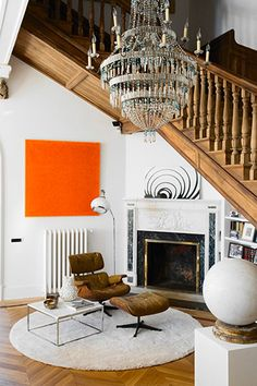 I love this caramel colour leather on the Eames Lounge chair, floating on a round raft of white carpet. Table, fireplace.