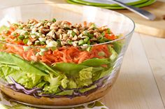 KRAFT Layered Asian Salad 1/2 C. KRAFT Asian Toasted Sesame Dressing 1/4 C. PLANTERS Creamy Peanut Butter 1 tsp. Sriracha sauce 3 C. shredded red cabbage 4 C.  chopped romaine lettuce 1 C. pea pods, sliced diagonally 2 carrots, shredded (about 1 cup) 4 green onions, sliced 1/2 C. PLANTERS Lightly Salted Dry Roasted Peanuts, chopped Whisk dressing, peanut butter, Sriracha sauce until blended. Spread in bottom of bowl. Layer remaining ingredients; toss before serving.