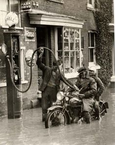 England 1935 - A gas station attendant fills the tank on a motorcycle carrying two people during a small flood. Everyone seems so chipper. Old Gas Pumps, Vintage Gas Pumps, Vintage Bikes, Vintage Cars, Retro Vintage, Motos Retro, Gas Station Attendant, Pompe A Essence, Old Gas Stations