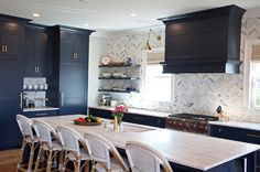 Benjamin Moore Hale Navy Kichen with Brass Accents. This navy kitchen, features an eye-catching navy blue kitchen island is fitted with gray and white quartzite countertops holding an undermount sink with a brass gooseneck facuet and seating five Serena & Lily Riviera Counter Stools. The island faces a wall covered in herringbone marble backsplash tiles holding three floating navy shelves and framing windows covered in bamboo roman shades flanking a navy hood hung over a Wolf range mounted…
