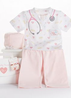 """Let this adorable baby nurse 3-piece layette set heal your wounds! This comfy and adorable scrubs-style bedtime layette comes with a short-sleeved top accented with yellow bandaids, blue crosses, deep-pink hearts, a stethoscope around the neck and """"Baby Nurse"""" embroidered on the left pocket, long pink pants, and pink surgical cap with white trim."""